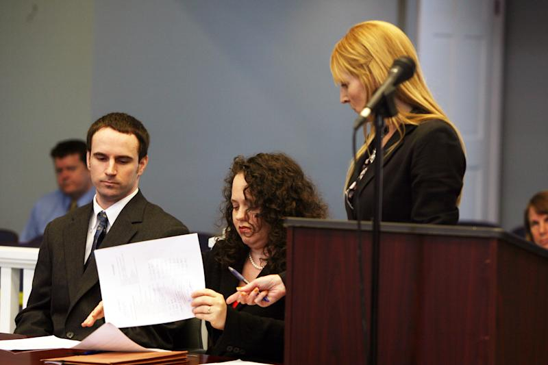 U.S. Army Pvt. Christopher Salmon, left, listens as his attorney Gabrielle Amber Pittman, center, and Assistant District Attorney Isabel Pauley go over a plea deal Thursday, April 3, 2014, in a Long County, Ga. courtroom. Salmon pleaded guilty to malice murder charges in the killing of former military colleague Michael Roark, and was sentenced to life in prison with no chance of parole. (AP Photo/Lewis Levine)