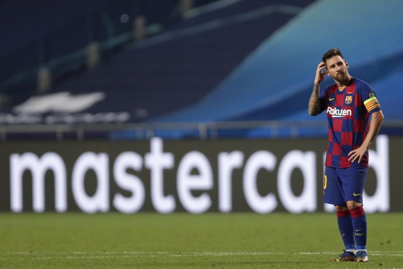 Lionel Messi scratches his head while standing on the pitch.