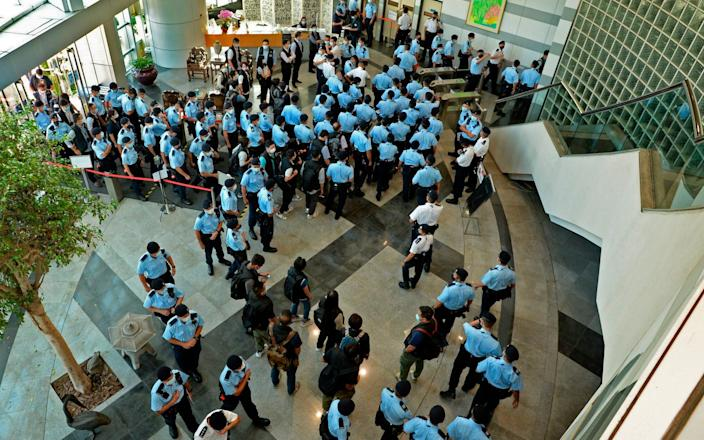 Police officers gather at the lobby of headquarters of Apple Daily in Hong Kong Thursday - Apple Daily