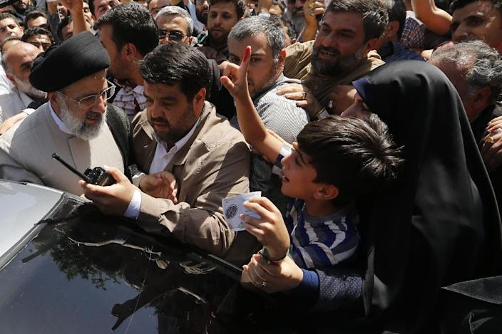 Presidential candidate Ebrahim Raisi greets supporters after voting in Tehran on May 19, 2017 (AFP Photo/ATTA KENARE)