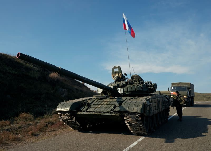 A service member of the Russian peacekeeping troops stands next to a tank in Nagorno-Karabakh