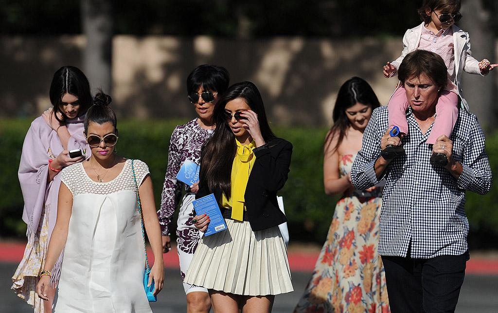 """After spending time with new beau Kanye West in New York City, Kim Kardashian reunited with her famous family to attend church together in Los Angeles on Easter. The """"Keeping Up With the Kardashians"""" star looked festive in a pastel-colored top and pleaded white mini. Bruce Jenner helped out mom-to-be Kourtney by giving her son, Mason, a lift as he clutched an egg. (4/8/2012)"""