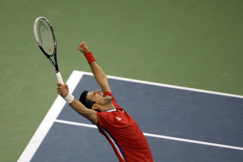 Serbia's Novak Djokovic throws his hands in the air and celebrates after defeating Czech Republic's Tomas Berdych at their Davis Cup Finals tennis match in Belgrade, Serbia, Sunday, Nov. 17, 2013.(AP Photo/ Marko Drobnjakovic)