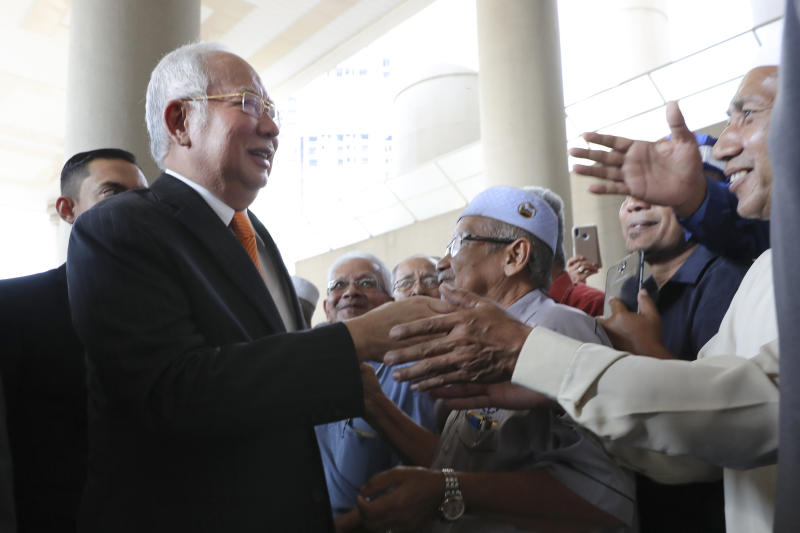 Former Malaysian Prime Minister Najib Razak, left, greets supporters as he arrives at Kuala Lumpur High Court in Kuala Lumpur, Malaysia, Monday, Nov. 11, 2019. An important court ruling Monday in the first corruption trial of Najib will be a test of the legal system and of the credibility of the prime minister who brought about his shocking ouster from office last year. (AP Photo/Vincent Thian)