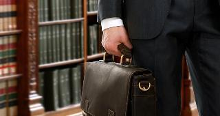Lawyer holding briefcase in library  copyright sheff/Shutterstock.com