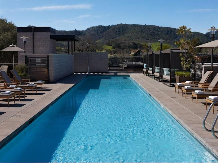 """If ever there was a perfect location for a Napa Valley hotel, this would be it. <a href=""""https://www.cntraveler.com/hotels/united-states/yountville/bardessono-napa-valley?mbid=synd_yahoo_rss"""" rel=""""nofollow noopener"""" target=""""_blank"""" data-ylk=""""slk:Here"""" class=""""link rapid-noclick-resp"""">Here</a>, you're at the heart of bustling Yountville and literal steps down the street from <a href=""""https://www.cntraveler.com/restaurants/yountville/french-laundry?mbid=synd_yahoo_rss"""" rel=""""nofollow noopener"""" target=""""_blank"""" data-ylk=""""slk:The French Laundry"""" class=""""link rapid-noclick-resp"""">The French Laundry</a>—and thanks to this elegant rooftop pool, all you see is sunshine, mountains and vineyards. Join one of the pool deck's morning yoga classes, then book a cabana and lounge the day away."""