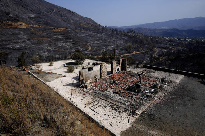 """A burnt house is seen on outskirts of Ora village, in the background is the Larnaca mountain region, Cyprus, Sunday, July 4, 2021. Cyprus' interior minister says four people have died in what he called the """"most destructive"""" fire in the island nation's history. (AP Photo/Petros Karadjias)"""