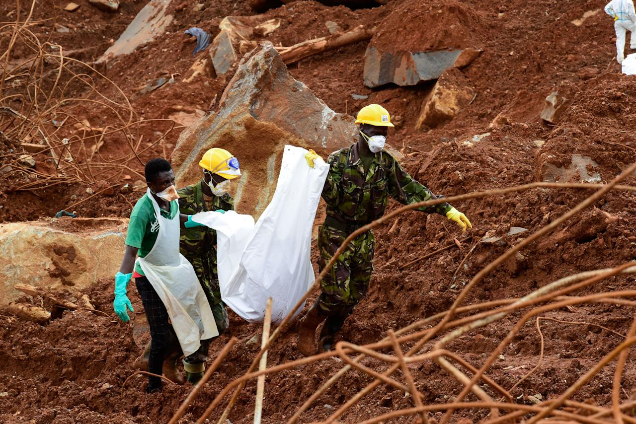 <p>A volunteer and soldiers carry a victim across the mud, days following the partial collapse of a hillside that swept away hundreds of homes in a neighborhood of the capital Freetown on Aug. 19, 2017.<br /> (Photo: Seyllou/AFP/Getty Images) </p>
