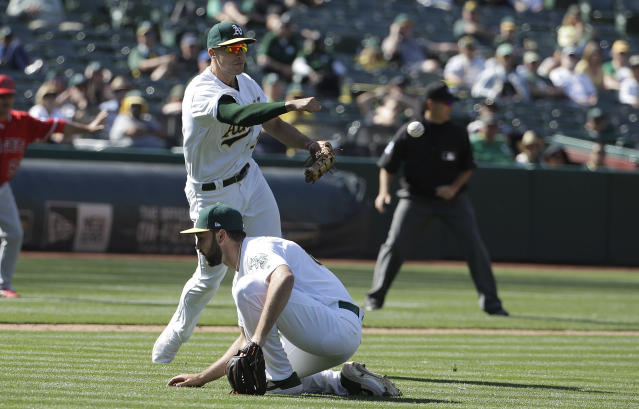 Oakland Athletics' Matt Olson, top, makes a throwing error that scored Los Angeles Angels' Cesar Puello during the eleventh inning of a baseball game in Oakland, Calif., Wednesday, May 29, 2019. (AP Photo/Jeff Chiu)