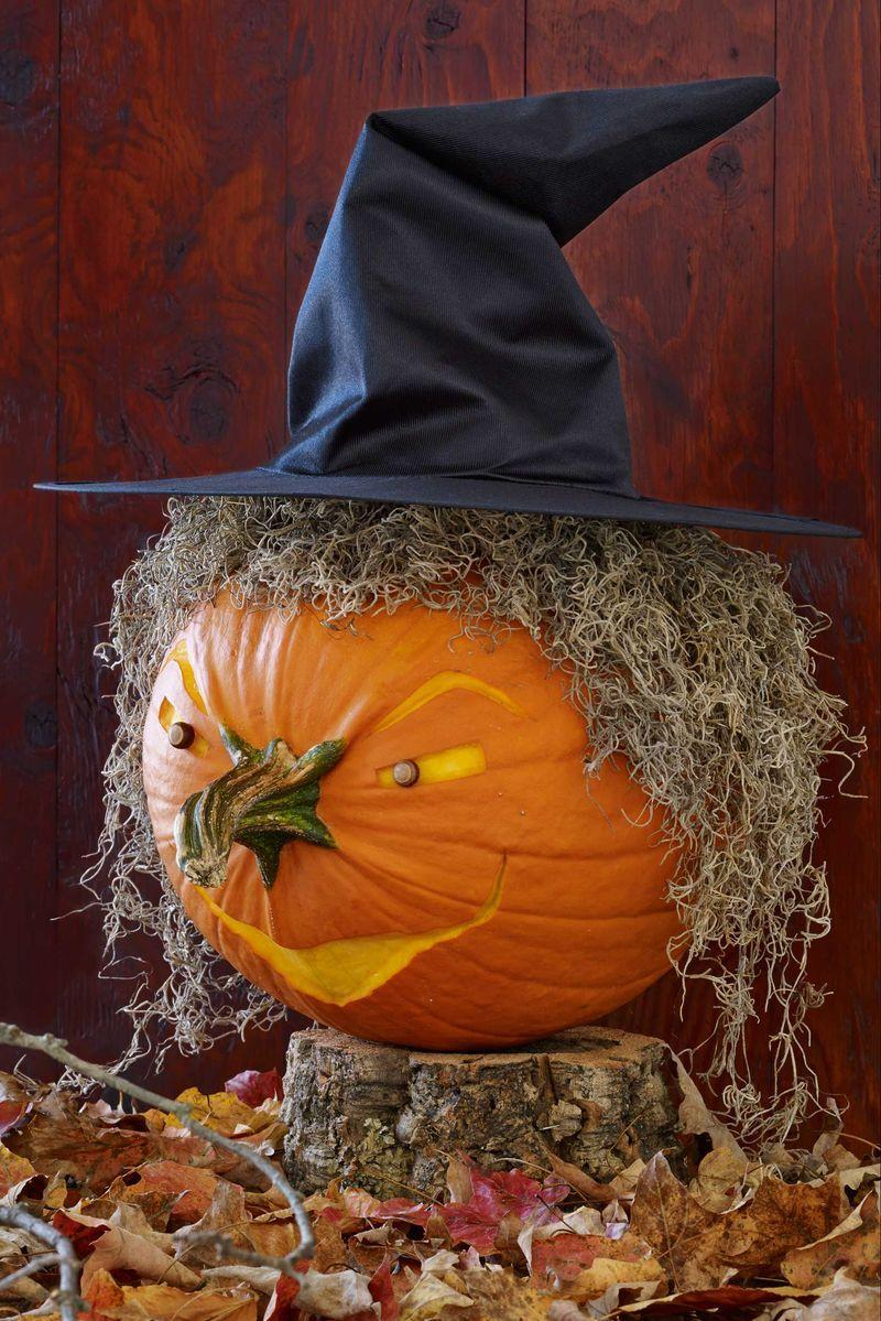 """<p>Position the pumpkin so the stem is centered where the nose should sit. (Tip: If the pumpkin wobbles, try securing an acorn or two at the base with hot glue to create anchoring feet). Using the washable marker, draw on eyes, eyebrows and a mouth. Try following the natural ribs of the pumpkin as a guide when deciding where to place the facial features, like the raised eyebrows or the curved mouth.</p><p>With the tip of the craft knife, scrape away the top layer of rind to reveal the lighter flesh underneath. Be careful not to poke all the way through to the inside of the pumpkin. Wipe away any excess marker with a damp paper towel. Remove the cap from two acorns and discard. Press each acorn into the flesh of an eye socket until it's secured.</p><p>Spread a bead of hot glue along the top and sides of the pumpkin where you want the hairline to be. Create the witch's mane by pressing on <a href=""""https://www.amazon.com/Mosser-Lee-ML0560-Spanish-Moss/dp/B000QTO78Q?tag=syn-yahoo-20&ascsubtag=%5Bartid%7C10070.g.950%5Bsrc%7Cyahoo-us"""" rel=""""nofollow noopener"""" target=""""_blank"""" data-ylk=""""slk:Spanish moss"""" class=""""link rapid-noclick-resp"""">Spanish moss</a>, adding enough so the orange rind is covered. Place the <span class=""""redactor-unlink"""">witch hat on top,</span> securing with bobby pins at the back, if necessary.</p><p><a class=""""link rapid-noclick-resp"""" href=""""https://www.amazon.com/Beistle-Satin-Soft-Black-Accessory-1-Count/dp/B000R4KNE2?tag=syn-yahoo-20&ascsubtag=%5Bartid%7C10070.g.950%5Bsrc%7Cyahoo-us"""" rel=""""nofollow noopener"""" target=""""_blank"""" data-ylk=""""slk:SHOP WITCH HAT"""">SHOP WITCH HAT</a></p>"""