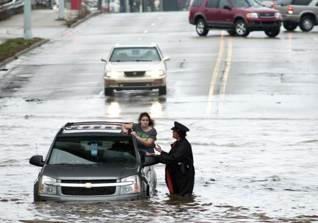 Police officer Shannon Vandenheuvel helps Barbara Jones from her partially submerged car in Grand Rapids, Mich. Thursday, April 18, 2013. Middle America was getting everything nature has to throw at it on Thursday, from snow in the north to tornadoes in the Plains, and with torrential rains causing floods and transportation chaos in several states. (AP Photo/Grand Rapids Press, Chris Clark)