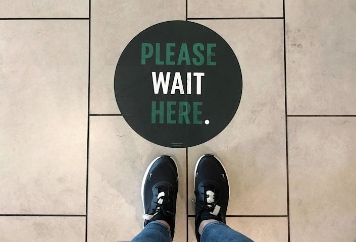 A social distancing measure sticker on the floor inside a Starbucks. (Photo: Naomi Baker via Getty Images)
