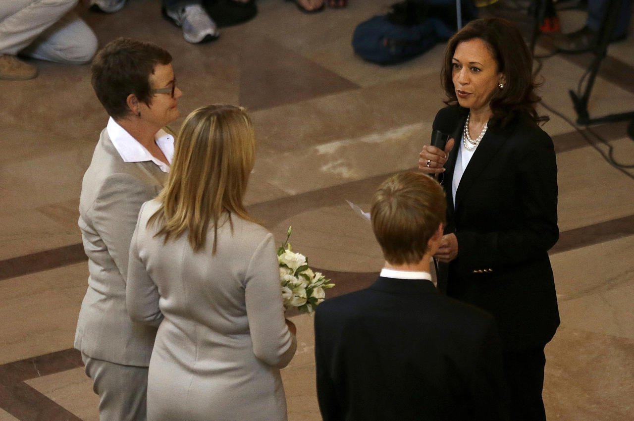 Attorney General Kamala Harris, right, officiates the wedding of Kris Perry, left, and Sandy Stier, second from left, in San Francisco, Friday, June 28, 2013. Stier and Perry were married Friday, June 28, 2013, after a federal appeals court on Friday cleared the way for the state of California to immediately resume issuing marriage licenses to same-sex couples after a 4 1/2-year freeze. (AP Photo/Jeff Chiu)