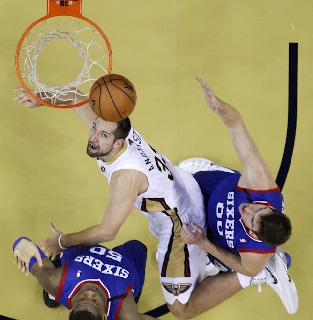New Orleans Pelicans power forward Ryan Anderson (33) drives to the basket between Philadelphia 76ers power forward Lavoy Allen (50) and center Spencer Hawes (00) in the first half of an NBA basketball game in New Orleans, Saturday, Nov. 16, 2013. (AP Photo/Gerald Herbert)
