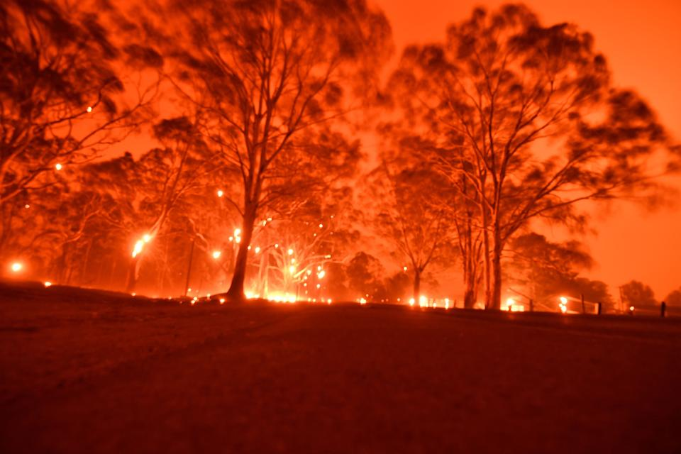 The afternoon sky glows orange from bushfires in the area around the town of Nowra in the Australian state of New South Wales on December 31. (Photo by SAEED KHAN/AFP via Getty Images)