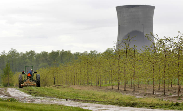 FILE - In this May 18, 2011 file photo, a worker drives a tractor at a tree farm in North Perry, Ohio, near the cooling towers of the Perry Nuclear Power Plant. According to an unreleased Government Accountability Office report obtained by The Associated Press, the facility had 8 higher-level violations and 256 lower-level violations between 2000-2012. Lower-level violations are those considered to pose very low risk, such as improper upkeep of an electrical transformer or failure to analyze a problem with no impact on a system's operation, such as the effect of a pipe break. Higher-level violations range from low to high safety significance, such as an improperly maintained electrical system that caused a fire and affected a plant's ability to shut down safely. (AP Photo/Amy Sancetta, File)