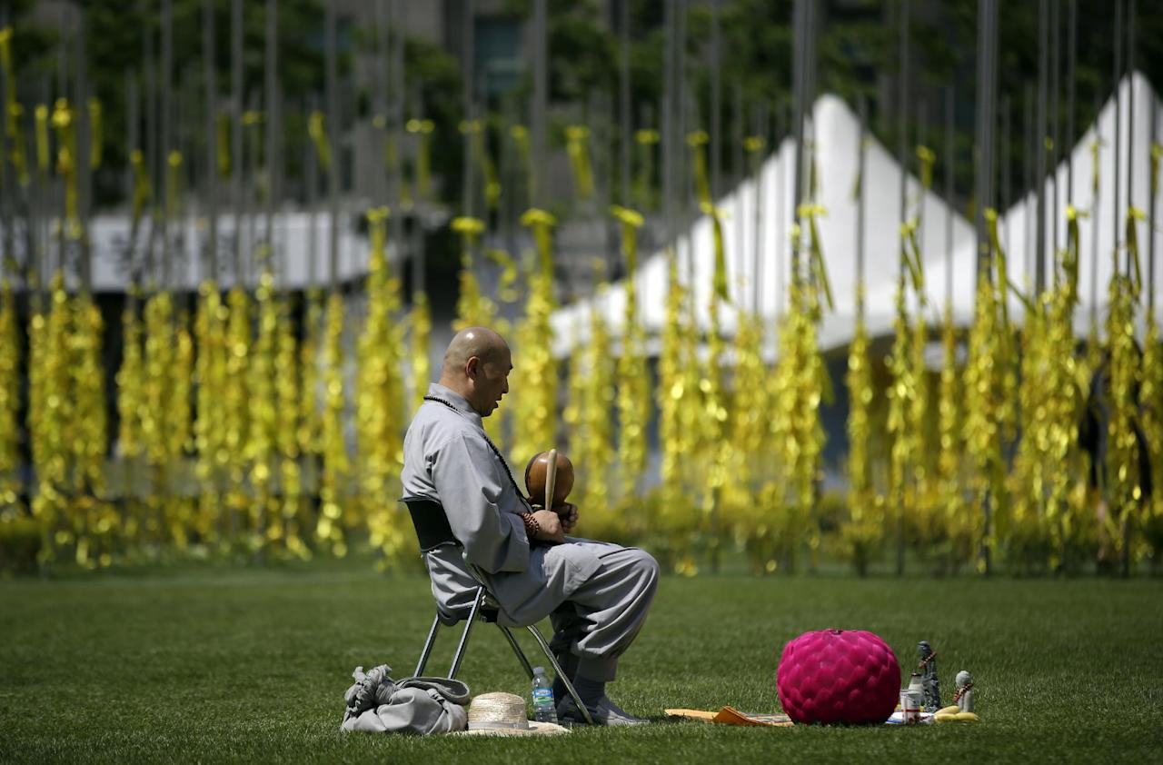 A Buddhist monk prays for the victims and missing passengers of the sunken ferry Sewol at a group memorial altar in Seoul, South Korea, Wednesday, May 7, 2014. The ferry disaster left more than 200 people dead, with others still missing. Government and civilian divers are fighting rapid currents as they try to retrieve the remaining bodies.(AP Photo/Lee Jin-man)