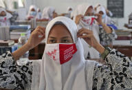 """Students adjust their face masks during a class where teaching about the health protocols for curbing the spread of coronavirus outbreak at Daarul Rahman Islamic Boarding School in Jakarta, Indonesia, Wednesday, Nov. 18, 2020. Writing on the mask reads """"Don't let your guard down, discipline yourself to always wear mask."""" (AP Photo/Tatan Syuflana)"""