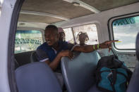 Jhon Celestin, his wife Delta De Leon and their daughter Chloe, deported from the United States a few days earlier, sit in a minibus, in Port-au-Prince, Haiti, Friday, Sept. 24, 2021. On their second day in Haiti, the couple decided to travel to Jacmel to visit relatives, a risky trip because it entails crossing gang-controlled territory. Buses often form convoys for safety, and sometimes pay gangs for safe passage. (AP Photo/Joseph Odelyn)