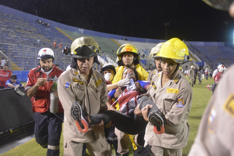 Firefighters carry away a fan affected by tear gas fired by police to break up deadly fights between fans before the start of a game between Motagua and Olimpia inside the national stadium in Tegucigalpa, Honduras, on Saturday.