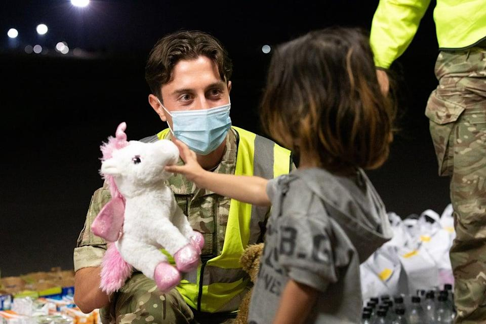 Military personnel handing out food, drink, toys, and blankets during Operation Pitting at RAF Brize Norton (Cpl Will Drummee RAF/MOD/Crown copyright) (PA Media)