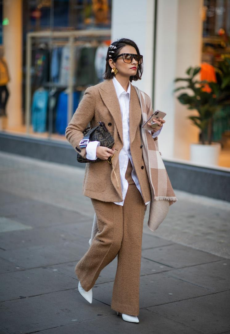 <p>A guest spotted arriving at the Natasha Zinko show in a beige woollen two-piece suit complete with hair barrettes and a Fendi bag. <em>[Photo: Getty]</em> </p>