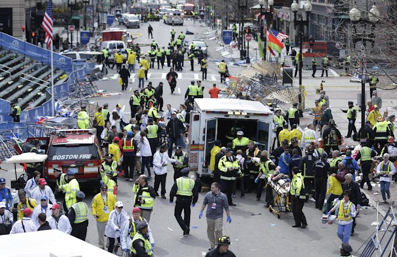FILE This April 15, 2013 file photo shows medical workers aiding injured people at the finish line of the 2013 Boston Marathon in Boston following an explosion. If the Obama administration seeks the death penalty against Boston Marathon bombing suspect Dzhokhar Tsarnaev, it would face a long, difficult legal battle with uncertain prospects for success in a state that hasn't seen an execution in nearly 70 years. Attorney General Eric Holder will have to decide several months before the start of any trial whether to seek death for Tsarnaev. It is the highest-profile death-penalty decision yet to come before Holder, who personally opposes the death penalty. (AP Photo/Charles Krupa, File)