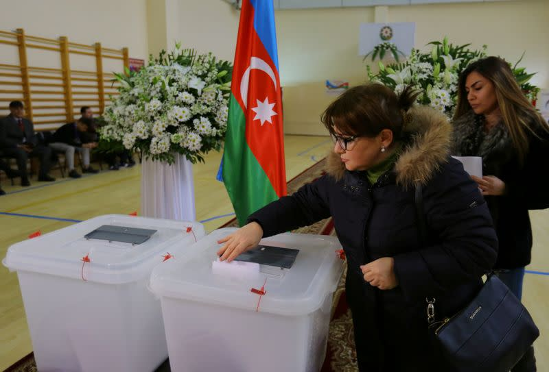 A woman casts her vote at a polling station during a snap parliamentary election in Baku
