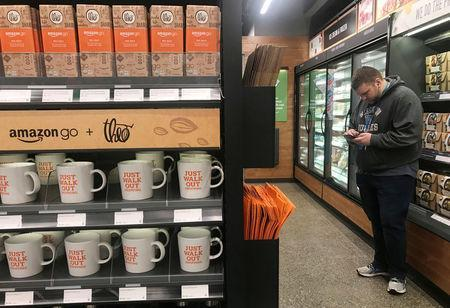 A shopper is seen using his phone in the line-free, Amazon Go store in Seattle, Washington, U.S., January 18, 2018. Photo taken January 18, 2018. REUTERS/Jeffrey Dastin