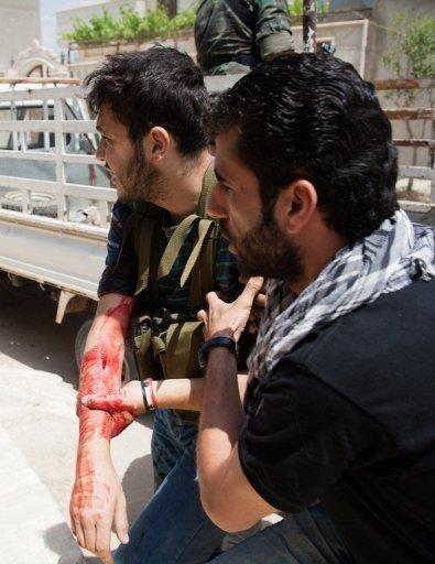 An injured Free Syrian Army fighter is taken to a hospital in Qusayr, on May 13, after heavy fighting broke out. Syrian troops have attacked a central rebel bastion, with dozens reportedly killed across the country, as the EU slaps fresh sanctions on Damascus