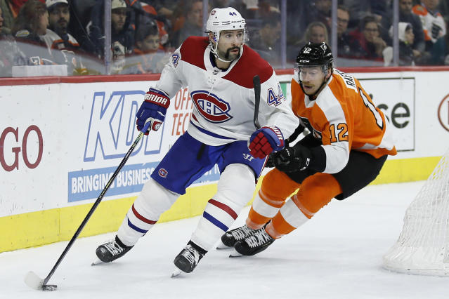 Montreal Canadiens' Nate Thompson (44) tries to keep Philadelphia Flyers' Michael Raffl (12) away from the puck during the second period of an NHL hockey game, Thursday, Nov. 7, 2019, in Philadelphia. (AP Photo/Matt Slocum)