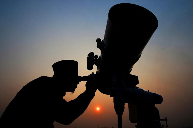 <p>An official looks through a telescope for the sighting of the new moon for the start of the Muslim fasting month of Ramadan at a religious boarding school in Jakarta, Indonesia, May 26, 2017. (Photo: Antara Foto/Rivan Awal Lingga/Reuters) </p>