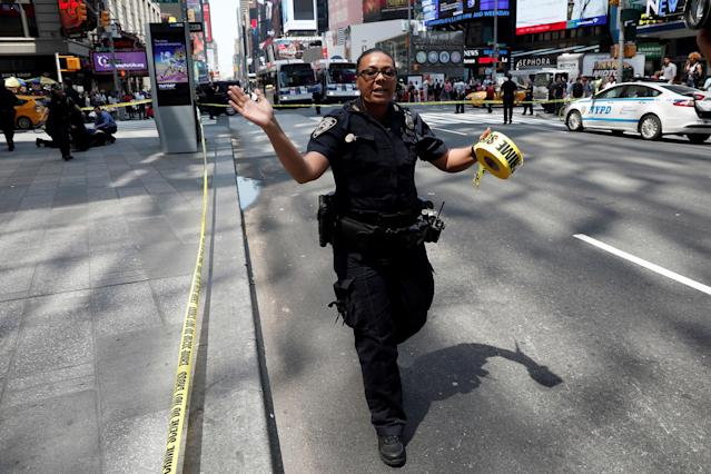 <p>A New York City Police (NYPD) officer motions people to get back in Times Square after a speeding vehicle struck pedestrians on the sidewalk in New York City on May 18, 2017. (Mike Segar/Reuters) </p>