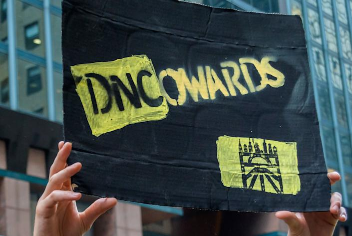 A Sunrise Movement activists holds up a sign outside the DNC headquarters. (Photo: Pacific Press via Getty Images)