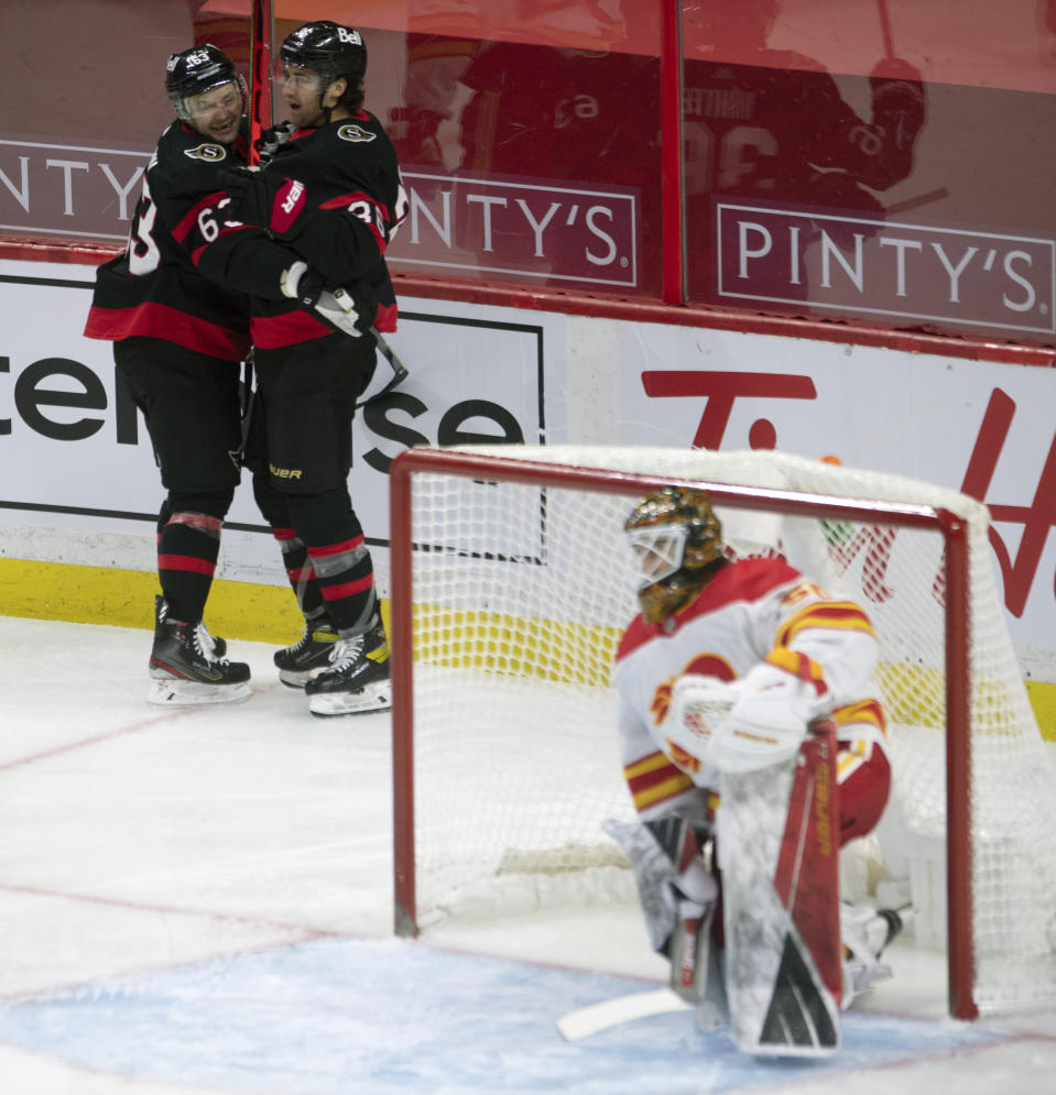Ottawa Senators center Colin White celebrates his goal with teammate right wing Evgenii Dadonov, left, as Calgary Flames goalie Artyom Zagidulin looks on from his crease during the third period of an NHL hockey game Thursday, Feb. 25, 2021, in Ottawa, Ontario. (Adrian Wyld/The Canadian Press via AP)
