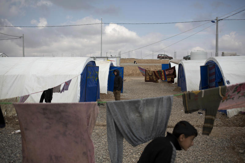 In this Thursday, Feb. 16, 2017 photo, residents from the western part of Mosul walk inside a camp east of the city. People who fled western Mosul in recent weeks say that residents are on the brink of starvation because is so little food left as a result of the ongoing operation to retake the city. (AP Photo/Bram Janssen)