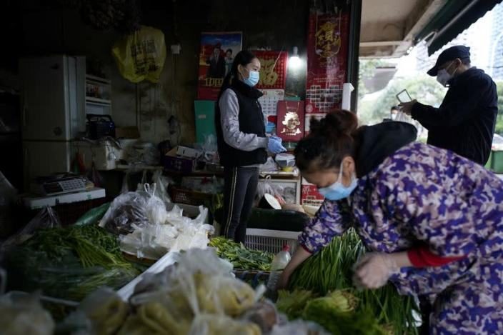 People wearing face masks buy vegetables at a street market in Wuhan