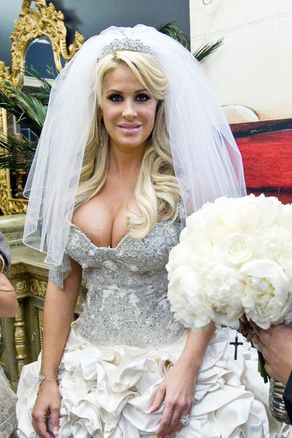 "<p>Not to be outdone, this <em>Real Housewives of Atlanta </em>star wore three dresses to her wedding to Kroy <span class=""redactor-unlink"">Biermann</span>. Her most extravagant (and revealing) was this low-cut, 32-pound Baracci Beverly Hills dress, which reportedly <a href=""http://www.dailymail.co.uk/tvshowbiz/article-2062430/Kim-Zolciak-wears-THREE-wedding-outfits-1-million-nuptials.html"" rel=""nofollow noopener"" target=""_blank"" data-ylk=""slk:set her back $58,000"" class=""link rapid-noclick-resp"">set her back $58,000</a>.</p>"