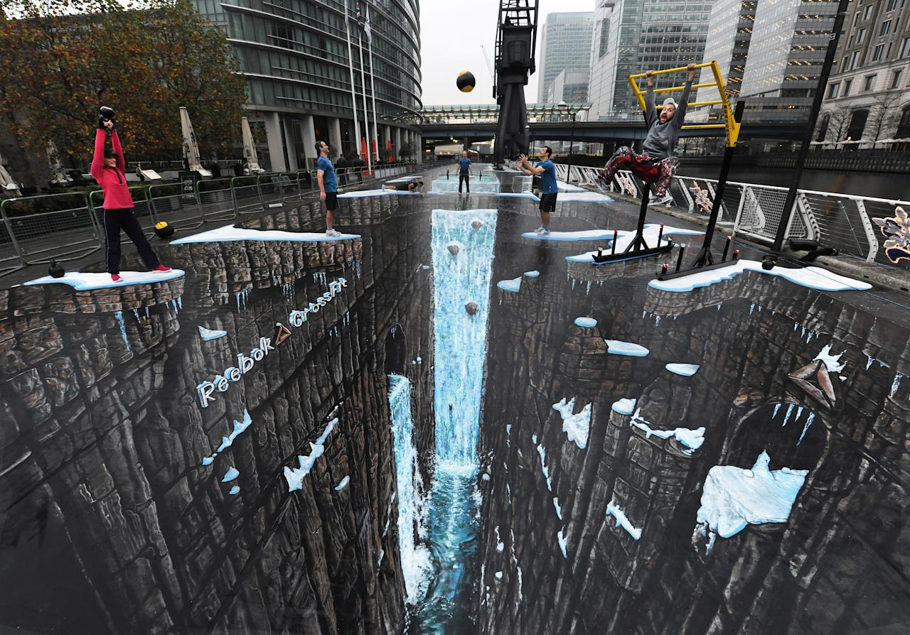 Commercial Photo - Reebok CrossFit, a revolutionary strength and conditioning programme, teamed up with artists 3D Joe and Max to break the Guinness World Record for the largest ever 3D street art. The painting measured an impressive 1,160.4 square metres and was unveiled at West India Quays, Canary Wharf, London, Thursday, Nov. 17, 2011. The public were invited to take part in a Reebok CrossFit WOD (workout of the day) on the spectacular artwork. ( Gary Prior/Reebok CrossFit via AP Images)