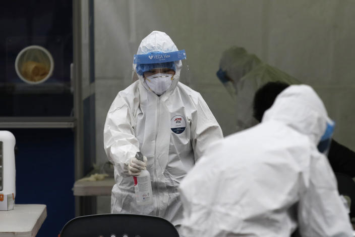 A medical worker wearing protective gears sprays disinfectant at a coronavirus testing site in Seoul, South Korea, Wednesday, Dec. 23, 2020. (AP Photo/Lee Jin-man)