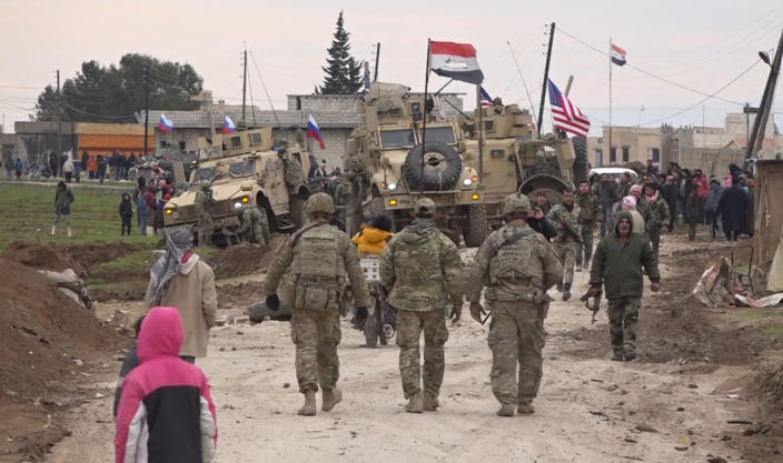 In this frame grab from video, Russian, Syrian and others gather next to an American military convoy stuck in the village of Khirbet Ammu, east of Qamishli city, Syria, Wednesday, Feb. 12, 2020. The Syrian official news agency SANA, said Wednesday, that locals had gathered at an army checkpoint, pelting the U.S. convoy with stones and taking down a U.S. flag flying on a vehicle when troops fired with live ammunition and smoke bombs. (AP Photo)