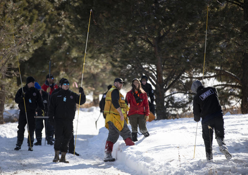 FILE - In this Feb. 13, 2020,file photo, El Paso County Law enforcement and volunteers use poles to search snowy areas for 11-year-old missing Colorado Springs boy Gannon Stauch on private property in southern Douglas County near Larkspur Colo. Human remains found in Florida are believed to be those of a Colorado boy reported missing in January by his stepmother, who was later arrested and charged with killing him, authorities said Friday, March 20, 2020.  . (Chancey Bush/The Gazette via AP, File)