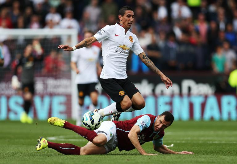 Manchester United's Angel di Maria (top) is tackled by Burnley''s Dean Marney during their English Premier League match at Turf Moor in Burnley, north-west England, on August 30, 2014