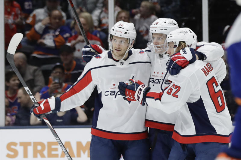 Washington Capitals' Nic Dowd (26) and Richard Panik (14) celebrate with teammate Carl Hagelin (62) after Hagelin scored a goal during the third period of an NHL hockey game against the New York Islanders Saturday, Jan. 18, 2020, in Uniondale, N.Y. The Capitals won 6-4. (AP Photo/Frank Franklin II)