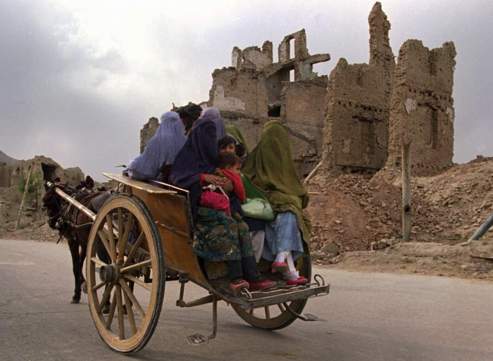 FILE -- In this Oct. 8, 1996 file photo, a horsecart carries a group of women with children to the market through a war-ruined section of Kabul. The Taliban fighters who rolled into Afghanistan's capital and other cities in recent days appear awestruck by the towering apartment blocks, modern office buildings and shopping malls. When the Taliban last seized power, in 1996, the country had been ravaged by civil war and the capital was in ruins. (AP Photo/John Moore, File)