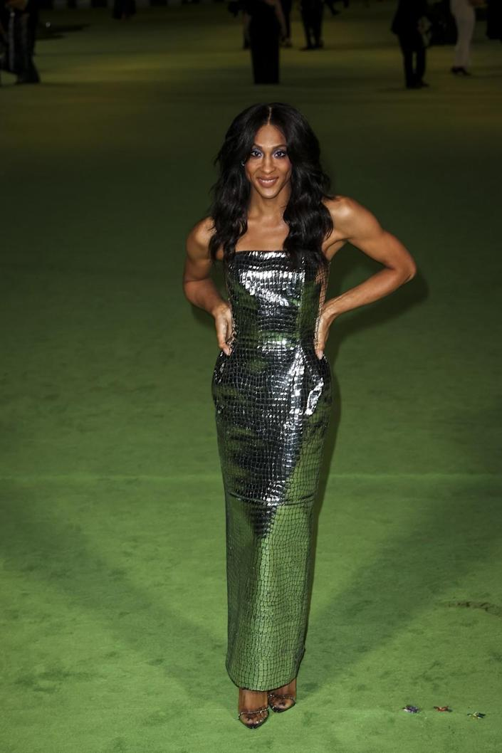 A woman in a silver dress posing on a green carpet