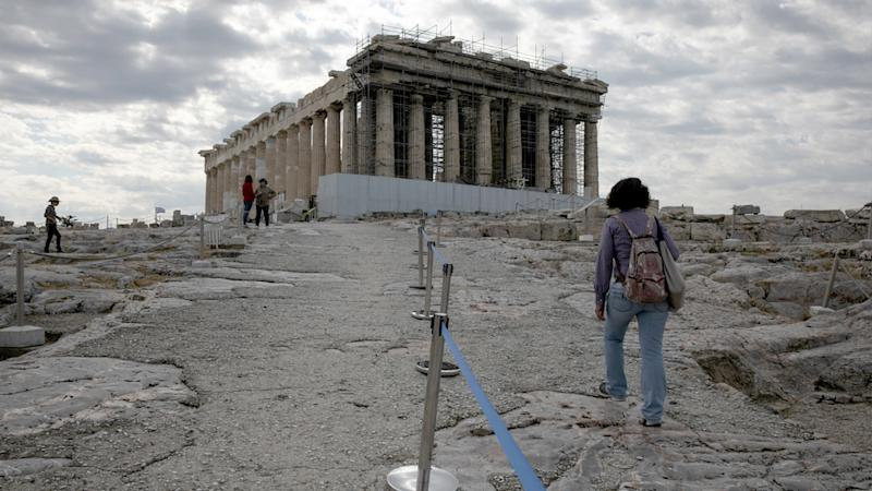 An employee of the Greek Culture ministry walks alongside a retractable belt separating visitors at the archaeological site of the Acropolis.