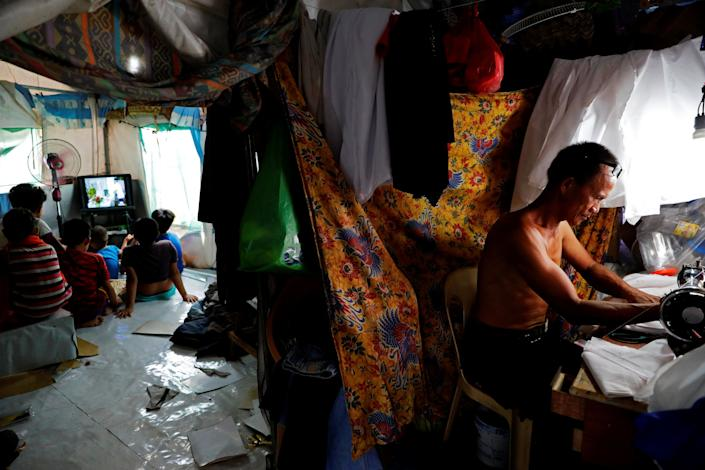 Abdul Gani, 49, works with a sewing machine as his children and nephews watch TV in a tent at an evacuation camp for families displaced by the Marawi siege, in Marawi City, Lanao del Sur province, Philippines. (Photo: Eloisa Lopez/Reuters)