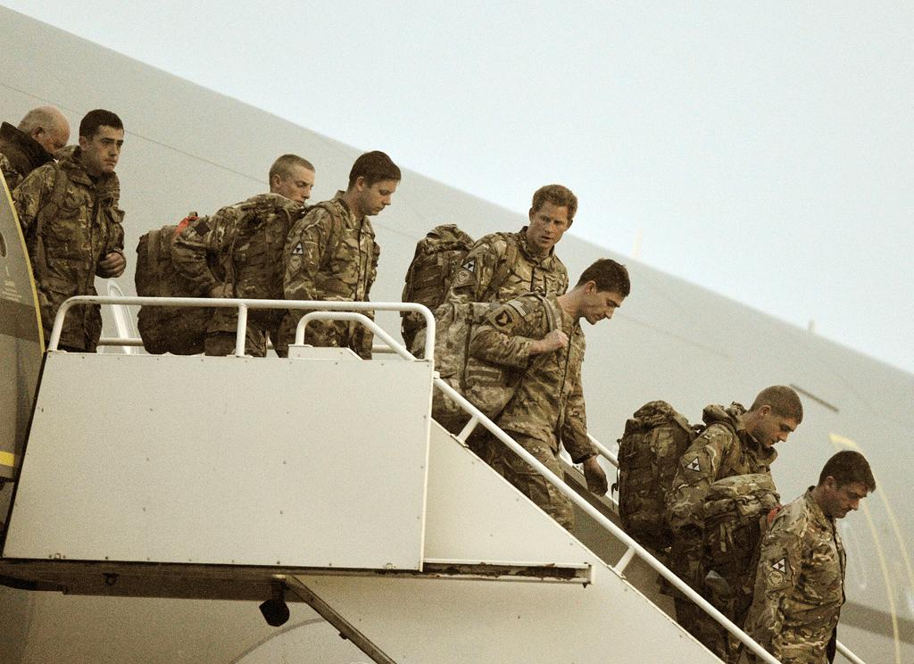 BRIZE NORTON, UNITED KINGDOM - JANUARY 23: Prince Harry (4th R) walks down the steps of a Royal Air Force A-330 transport aircraft as he arrives at RAF Brize Norton on January 23, 2013  in Oxfordshire, England. The prince is arrving back in the UK following the completion of his 20 week tour of duty in Afghanistan as an Apache Helicopter Pilot/Gunner with 662 Squadron of the Army Air Corps. (Photo by John Stillwell - WPA Pool/Getty Images)