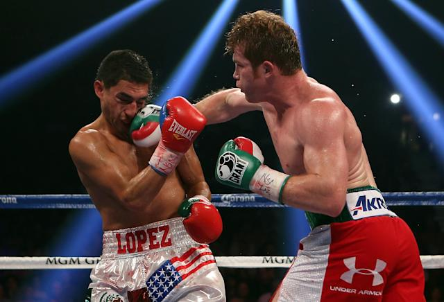 LAS VEGAS, NV - SEPTEMBER 15: (R-L) Canelo Alvarez lands a right to the head of Josesito Lopez during their WBC super welterweight title fight at MGM Grand Garden Arena on September 15, 2012 in Las Vegas, Nevada. (Photo by Josh Hedges/Getty Images)